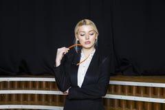 Красивая белокурая коммерсантка с тучными губами на офисе просторной квартиры в оранжевых стеклах и костюме владение домашнего кл Стоковые Фото