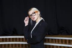 Красивая белокурая коммерсантка с тучными губами на офисе просторной квартиры в оранжевых стеклах и костюме владение домашнего кл Стоковая Фотография RF