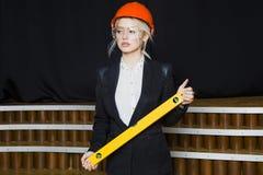 Красивая белокурая коммерсантка с ярусом применения на офисе просторной квартиры в оранжевых шлеме и костюме конструкции Стоковое Изображение