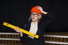 Красивая белокурая коммерсантка с ярусом применения на офисе просторной квартиры в оранжевых шлеме и костюме конструкции Стоковые Фотографии RF
