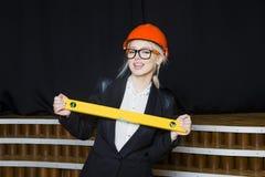 Красивая белокурая коммерсантка с ярусом применения на офисе просторной квартиры в оранжевых шлеме и костюме конструкции Стоковое фото RF