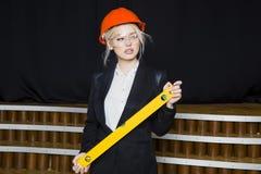 Красивая белокурая коммерсантка с ярусом применения на офисе просторной квартиры в оранжевых шлеме и костюме конструкции Стоковые Изображения RF