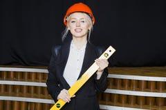 Красивая белокурая коммерсантка с ярусом применения на офисе просторной квартиры в оранжевых шлеме и костюме конструкции Стоковые Фото