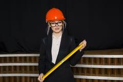 Красивая белокурая коммерсантка с ярусом применения на офисе просторной квартиры в оранжевых шлеме и костюме конструкции Стоковое Фото