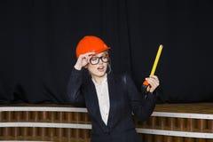 Красивая белокурая коммерсантка с ярусом применения на офисе просторной квартиры в оранжевых шлеме и костюме конструкции Стоковые Изображения