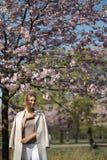 Красивая белокурая молодая женщина в парке вишневого цвета Сакуры весной наслаждаясь природой и свободным временем во время ее пу стоковые изображения