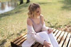 Красивая белокурая молодая женщина в парке вишневого цвета Сакуры весной наслаждаясь природой и свободным временем во время ее пу стоковое изображение rf