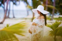 Красивая беременная девушка в белом платье и широк-наполненной до краев шляпе на пляже около пальм Стоковые Фото