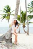 Красивая беременная девушка в белом платье и широк-наполненной до краев шляпе на пляже около пальм Стоковая Фотография RF