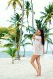Красивая беременная девушка в белом платье и широк-наполненной до краев шляпе на пляже около пальм Стоковое фото RF