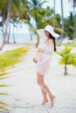 Красивая беременная девушка в белом платье и широк-наполненной до краев шляпе на пляже около пальм Стоковая Фотография