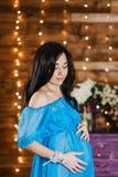 Красивая беременная женщина брюнет в silk голубом положении и взглядах платья на животе в студии стоковое фото