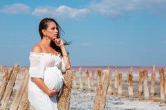 Красивая беременная женщина в природе в белом платье стоковая фотография rf
