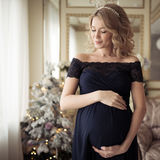 Красивая беременная женщина в платье праздника стоковое фото
