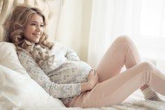 Красивая беременная женщина в уютных одеждах стоковые изображения