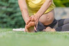 Красивая беременная женщина делая пренатальную йогу на природе Стоковые Фотографии RF