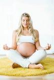Красивая беременная женщина делая йогу дома Стоковая Фотография