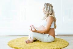 Красивая беременная женщина делая йогу дома Стоковые Фото
