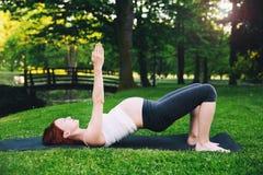 Красивая беременная женщина делая пренатальную йогу на природе outdoors Стоковое Изображение RF