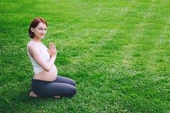 Красивая беременная женщина делая пренатальную йогу на природе outdoors Стоковые Изображения