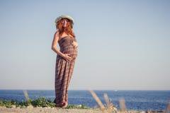 Красивая беременная женщина ослабляя около моря Стоковые Изображения