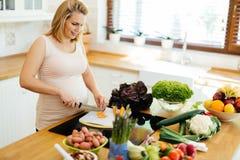 Красивая беременная женщина подготавливая еду стоковое фото rf