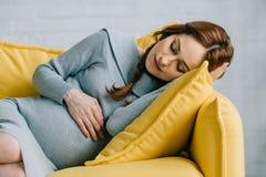 красивая беременная женщина спать на желтой софе стоковое изображение rf