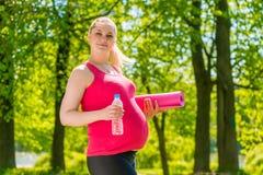 Красивая беременная женщина с циновкой йоги стоковые изображения