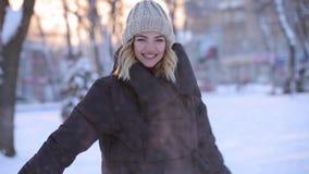 Красивая беспечальная женщина бросает снежный ком в парке зимы, slowmotion видеоматериал