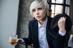 Красивая белокурая девушка выпивая в кафе Стоковое Изображение