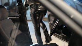 Красивая белокурая девушка в кожаных брюках выходит автомобиля сток-видео