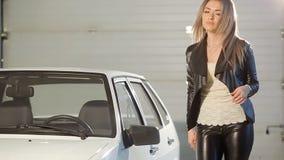 Красивая белокурая девушка в кожаных брюках выходит автомобиля видеоматериал
