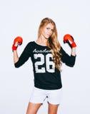 Красивая белокурая девушка в красных перчатках бокса представляя на белой предпосылке Поднятые руки крыто цвет теплый стоковые фото