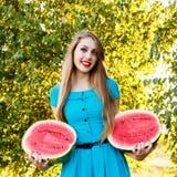Красивая белокурая девушка держа 2 половины отрезанного арбуза Стоковые Фотографии RF