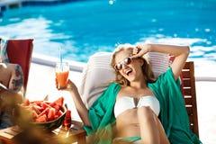 Красивая белокурая девушка загорая, выпивая коктеиль, лежа около бассейна Стоковая Фотография