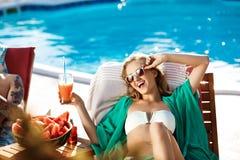 Красивая белокурая девушка загорая, выпивая коктеиль, лежа около бассейна Стоковое Изображение