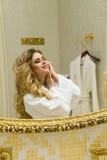Красивая белокурая девушка исправляет ее волосы и смотреть в зеркале в ее ванной комнате Молодая женщина красоты исправляет ее во Стоковые Изображения