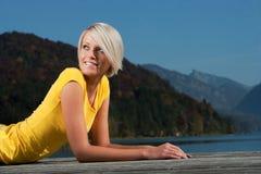 Красивая белокурая девушка ослабляя на деревянной моле Стоковая Фотография RF