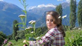 Красивая белокурая девушка сидя в поле цветков видеоматериал