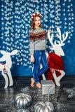 Красивая белокурая девушка стоя против стен с гирляндами Стоковое Фото