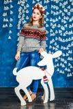 Красивая белокурая девушка стоя против стен с гирляндами Стоковые Фотографии RF
