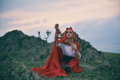 Красивая белокурая девушка с красным плащем на ее голове сидя на утесе стоковое изображение rf