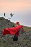 Красивая белокурая девушка с красным плащем на ее голове сидя на утесе стоковая фотография