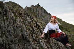 Красивая белокурая девушка с красным плащем на ее голове сидя на утесе стоковые фотографии rf