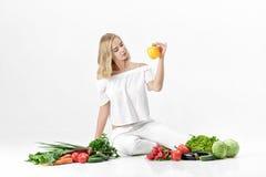 Красивая белокурая женщина в белых одеждах и сериях свежих овощей на белой предпосылке Девушка держит болгарский перец Стоковые Изображения
