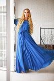Красивая белокурая женщина в длинном платье около лестниц Стоковая Фотография RF
