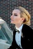 красивая белокурая женщина в костюме черноты человека с бабочки фонтаном почти Стоковое Фото