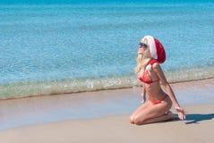 Красивая белокурая женщина в красной шляпе рождества и бикини на море приставают к берегу стоковая фотография