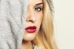 Красивая белокурая женщина в клобуке. красные губы Стоковые Изображения RF