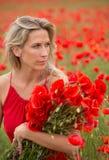 Красивая белокурая женщина в поле мака с цветками Стоковые Фотографии RF